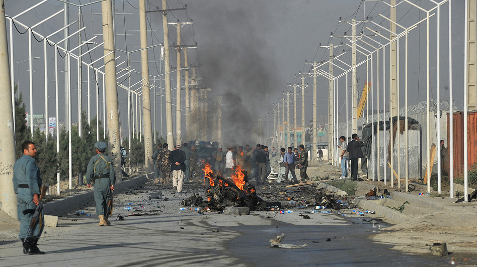 Afghan police and officials visit the site of a suicide attack in Kabul in September. A suicide bomber blew himself up alongside a minivan carrying foreigners on a major highway leading to the international airport in the Afghan capital, police said, killing at least 10 people, including nine foreigners. (AFP/Getty Images)