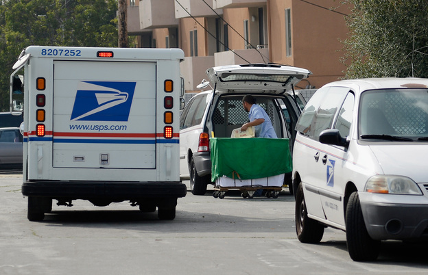 A U.S. Postal service employee loads his van as he prepares to leave the loading dock to deliver mail from the Los Feliz Post Office in Los Angeles.