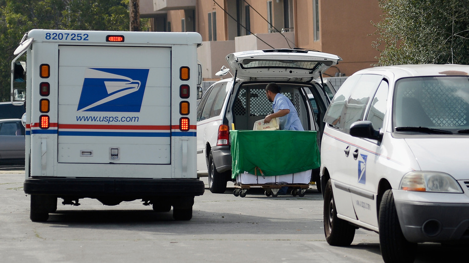 A U.S. Postal service employee loads his van as he prepares to leave the loading dock to deliver mail from the Los Feliz Post Office in Los Angeles. (Getty Images)