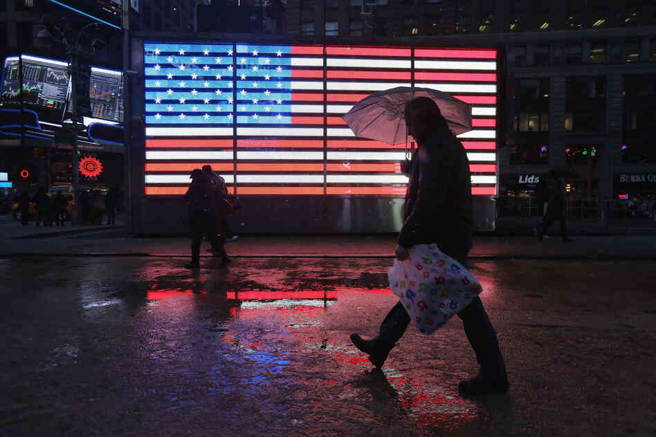 People walk through Times Square as a major winter storm moves in on Friday in New York City. Snow and freezing rain fell over Midtown Manhattan as the city braced for the major storm.