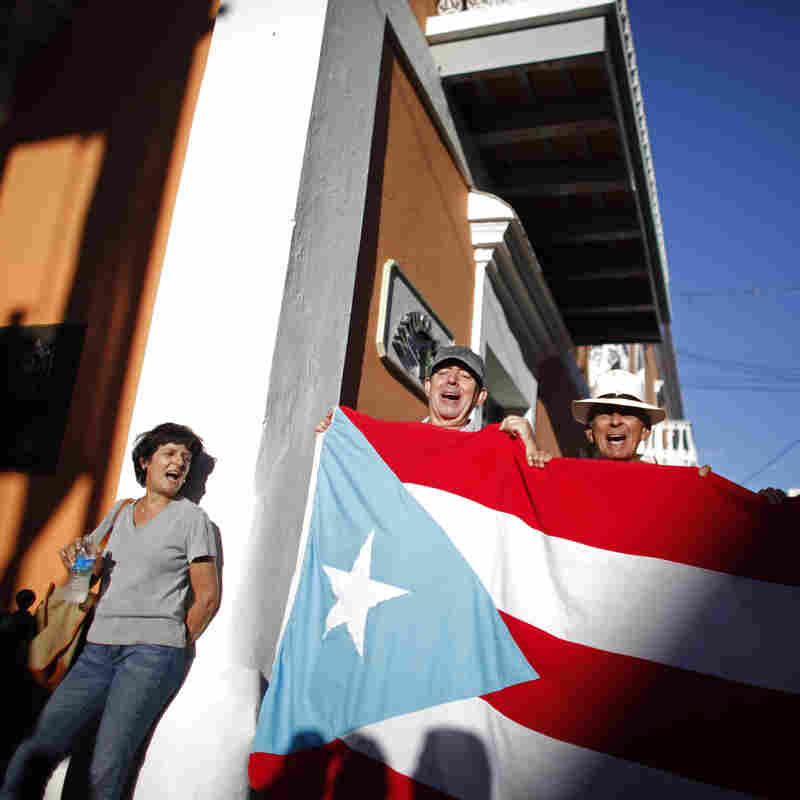 Demonstrators shout against plans to privatize the airport as they carry a Puerto Rican flag near the governor's office in San Juan, Puerto Rico, Wednesday, Feb. 6, 2013. Protesters are demanding the island's largest international airport not be privatized to an investment group.