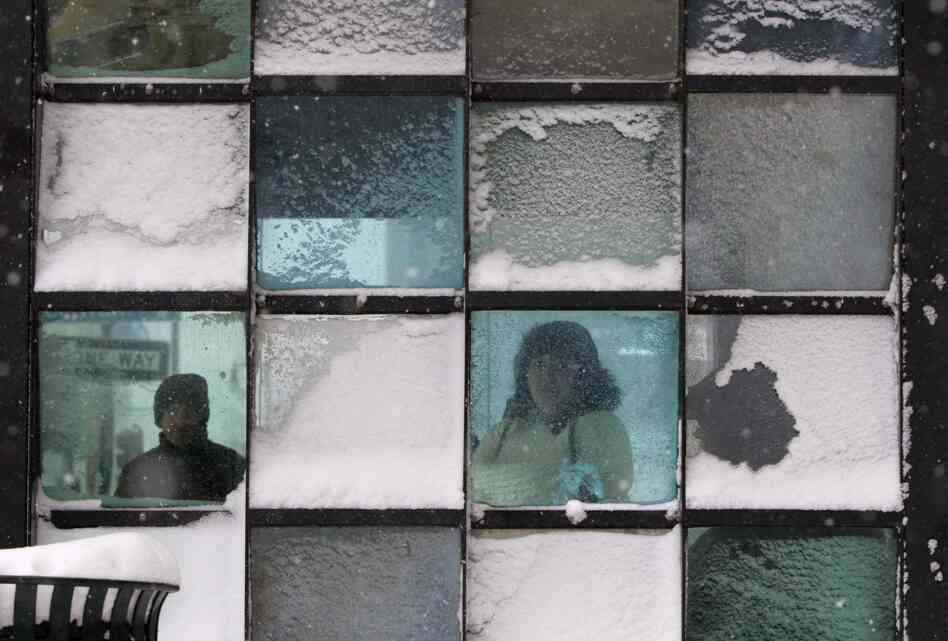 Riders wait in a bus stop where color-tinted windows collect snow during a storm in Portland, Maine. The storm sweeping into Maine already has dumped half a