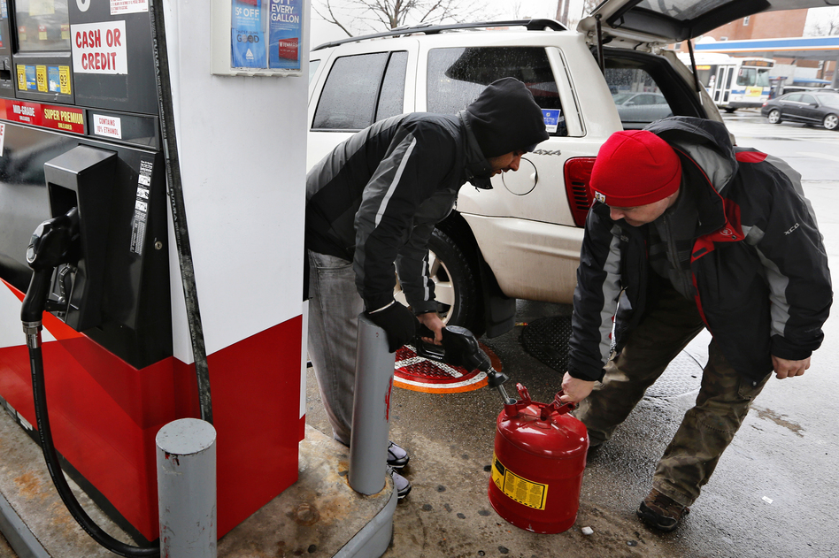 Men fill up a gas tank at a fueling station in Queens, N.Y. Blizzard warnings were in effect from New Jersey through southern Maine, with Boston expected to bear the brunt of the massive storm that could set records. (Reuters/Landov)