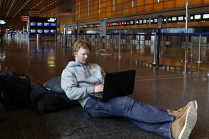 Rasmus Thomsen of Denmark works on his computer as he waits at Boston's Logan International Airport after flights were canceled or delayed.