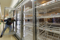 Jack Percoco reaches into depleted shelves for milk at a supermarket in Somerville, Mass.