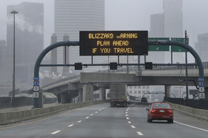 A warning sign flashes for motorists on the expressway into Boston as snow starts to fall on Friday.