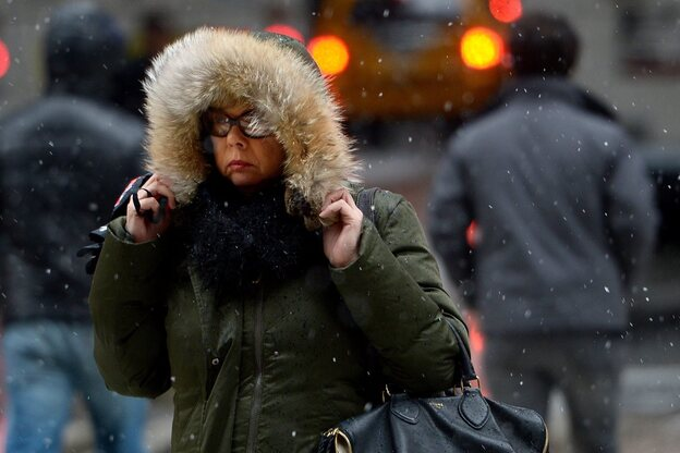Trying to stay warm, a woman in New York City clung on to her hood Friday.
