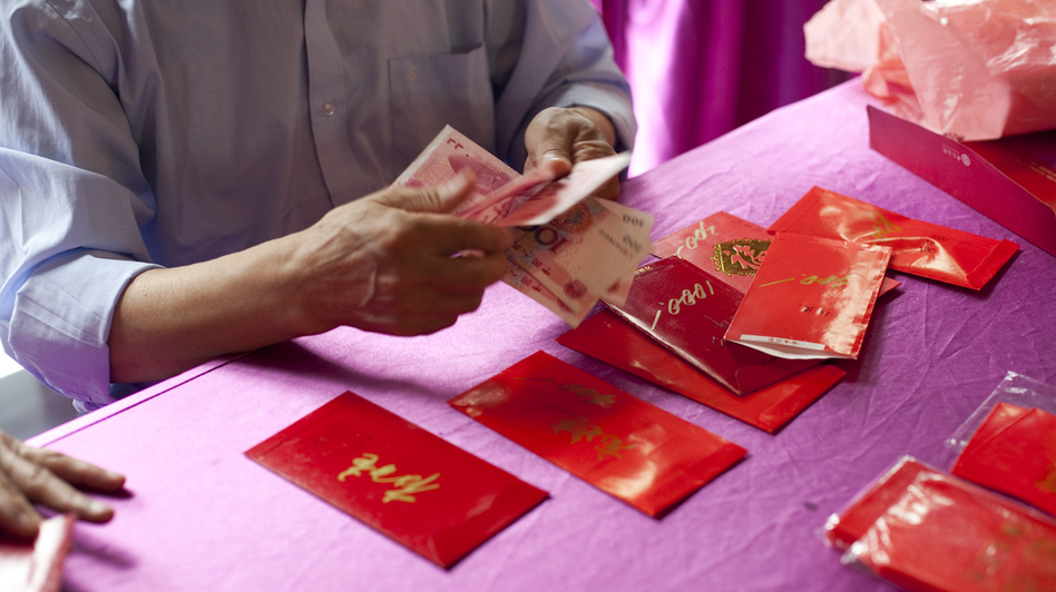 A man counts yuan to fill red envelopes in Beijing. Many families celebrate the Lunar New Year by exchanging small envelopes filled with money. (NPR)