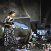 A woman tries to salvage items from a burnt out Sufi shrine outside the Tunisian capital, Tunis, last October. Hard-line Islamists, known as Salafists, have attacked many Sufi shrines in Tunisia recently.