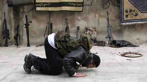 A Syrian rebel prays on a street in the northern city of Aleppo in January. Many Syrians are debating what role Islam should play in Syria if the current secular government is toppled.