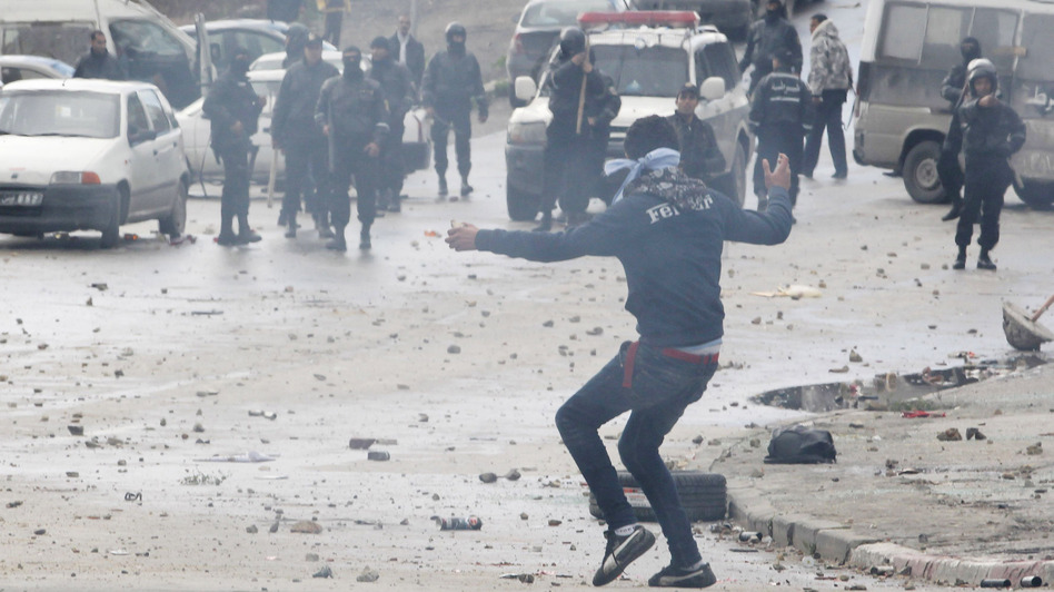 A protester, and riot police in the background, during the clashes Friday in Tunis. (Reuters /Landov)