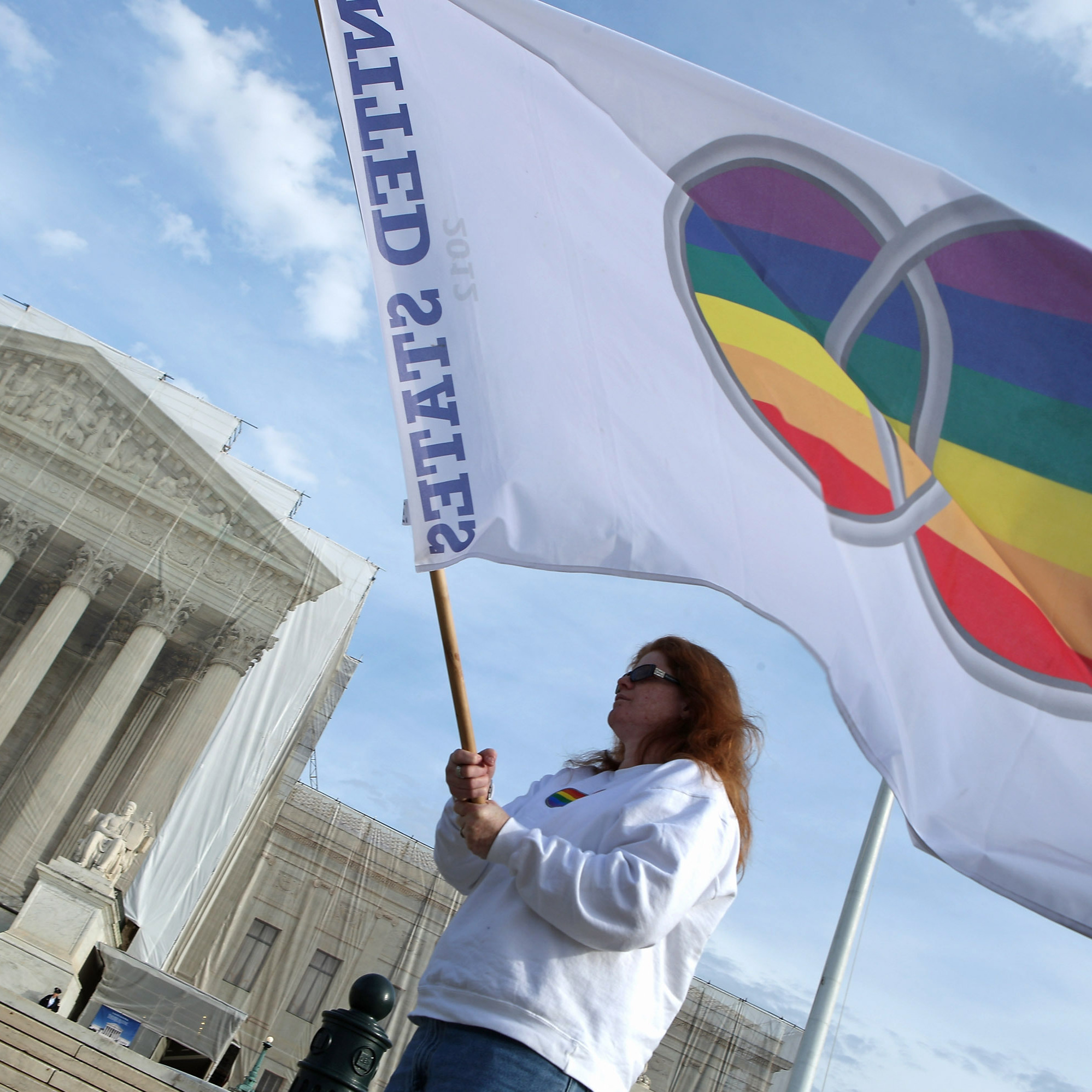 Kat McGuckin of Oaklyn, N.J., holds a gay pride flag while standing in front of the U.S. Supreme Court on Nov. 30.