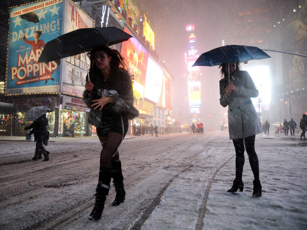 Two women look for a taxi in New York's Times Square on Friday.