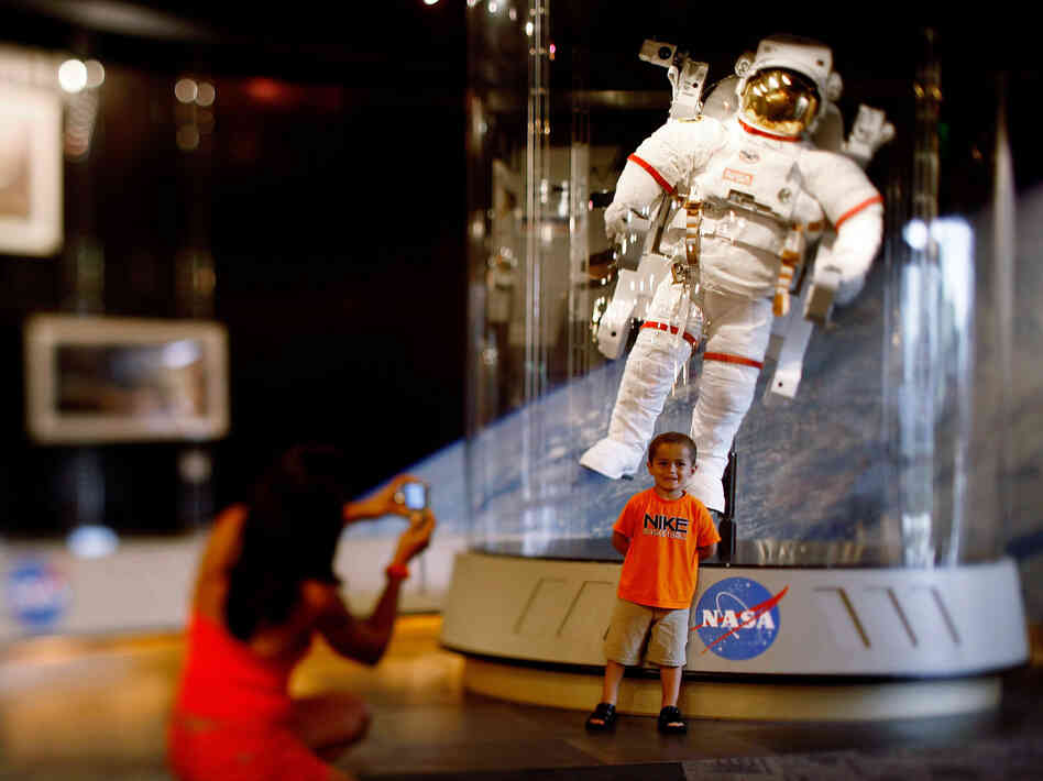 A child poses for a picture in front of an astronaut space suit at the Kennedy Space Center on the eve of the launch of Space Shuttle Endeavour July 14