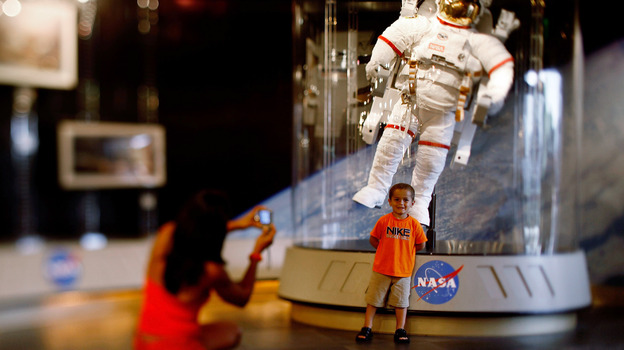 A child poses for a picture in front of an astronaut space suit at the Kennedy Space Center on the eve of the launch of Space Shuttle Endeavour July 14, 2009 in Cape Canaveral, Fla. (Getty Images)