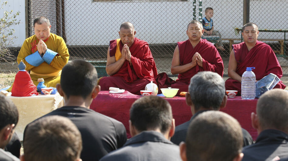 Telo Tulku Rinpoche, left, prays with Buddhist monks in front of inmates in a prison colony in Kalmykia, Russia, on Sept. 7, 2010. After renouncing his monkhood, Telo Rinpoche can no longer wear traditional robes, but still serves as the region's Tibetan Buddhist spiritual leader. (AP)