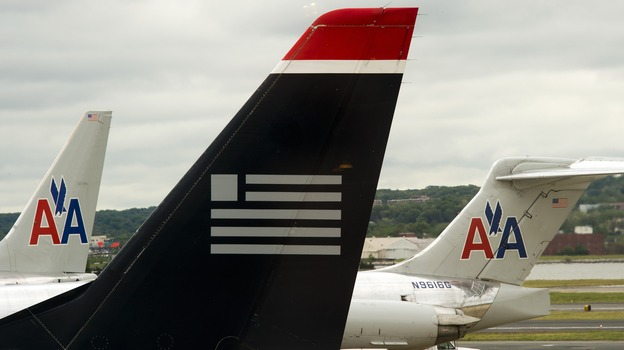 A US Airways plane rests near two American Airlines jets at Ronald Reagan Washington National Airport last year. The combined carrier would be named American Airlines. (AFP/Getty Images)