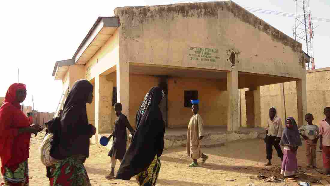 Women walk past the polio vaccine dispensary in Kano, Nigeria, where gunmen killed female health workers last Friday.