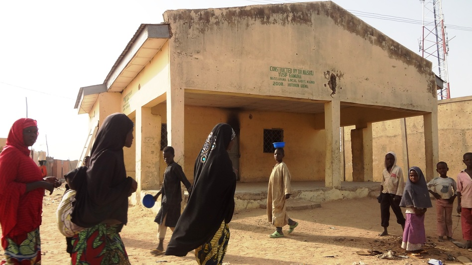 Women walk past the polio vaccine dispensary in Kano, Nigeria, where gunmen killed female health workers last Friday. (AFP/Getty Images)