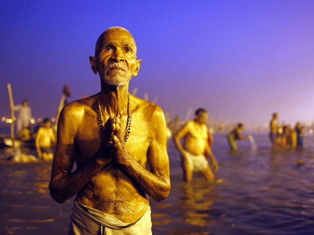 "A Hindu devotee prays after a holy dip at the Sangam, the confluence of three holy rivers — the Ganges, the Yamuna and the mythical Saraswati --"" during the Kumbh Mela festival in Allahabad, India, on Sunday."