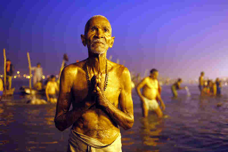 A Hindu devotee prays after a holy dip at