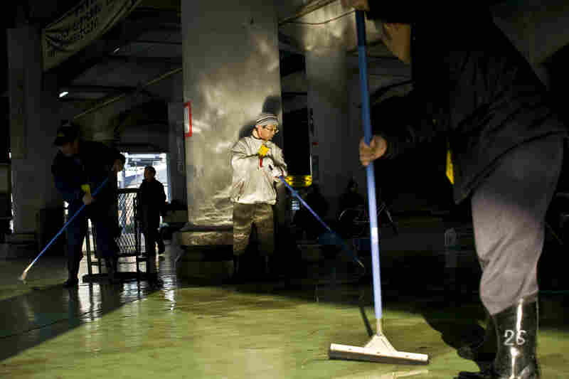 Men mop the floor of a labor center, which is sponsored by the government and provides the main source of income to a select few in Kamagasaki. People used to be able to get high-paying jobs in this town, but now there is no work, especially for the aging male population.