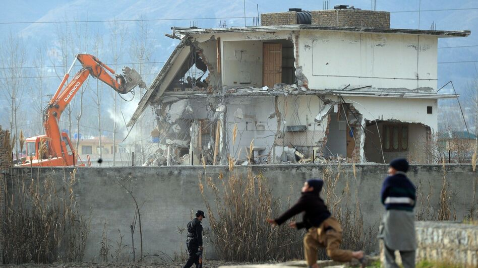 Young Pakistani boys play near demolition works while Osama bin Laden's compound in Pakistan is demolished. (AFP/Getty Images)
