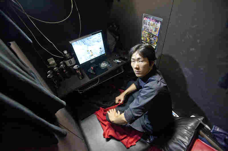 Chapter 4: Internet Cafe Refugees. Fumiya, 26, a security guard, has lived in an Internet cafe for 10 months. People live in the 24-hour cafe's small rooms, unable to afford rent anywhere else. Fumiya pays about $25 a day for a tiny private booth, a shared bathroom and laundry service.