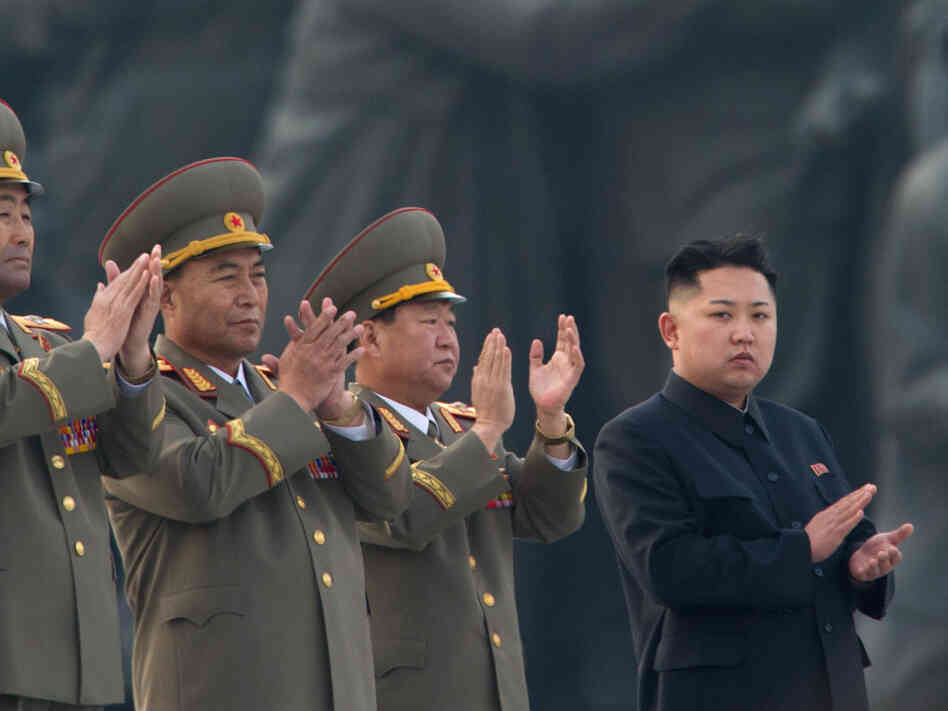 North Korean leader Kim Jong Un (right) claps during a ceremony unveiling statues honoring his grandfather and father, Kim Il Sung and Kim Jong Il, respectively, in Pyongyang last April.