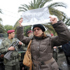 Tunisian soldiers stand guard as a woman holds up a poster featuring opposition leader Chokri Belaid during his funeral procession in a suburb of Tunis on Feb. 8. Belaid's assassination has laid bare the political rifts in post-revolutionary Tunisia.