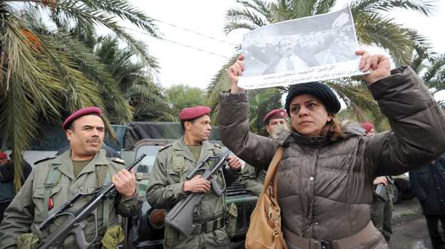 Tunisian soldiers stand guard as a woman holds up a poster featuring opposition leader Chokri Belaid during his funeral procession in a suburb of Tunis on Feb. 8. Belaid's assassination has laid bare the political rifts in post-revolutionary Tunisia. (AFP/Getty Images)