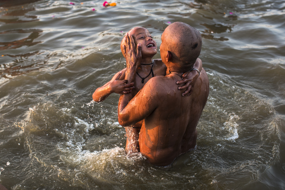 A father dips his son into the holy waters. (Getty Images)
