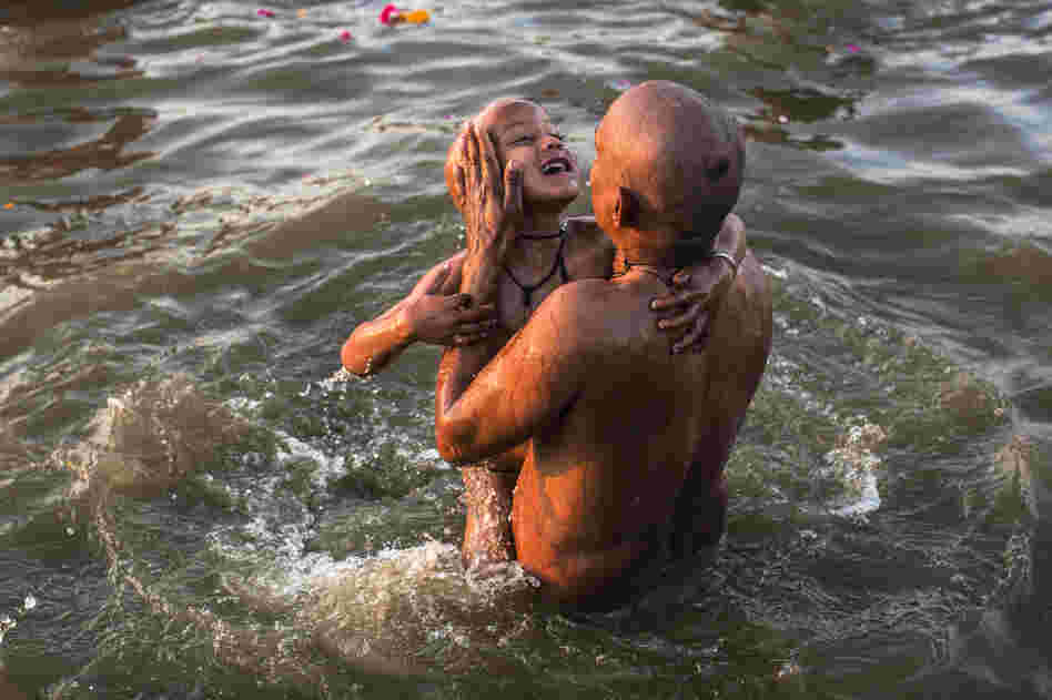 A father dips his son into the holy waters.