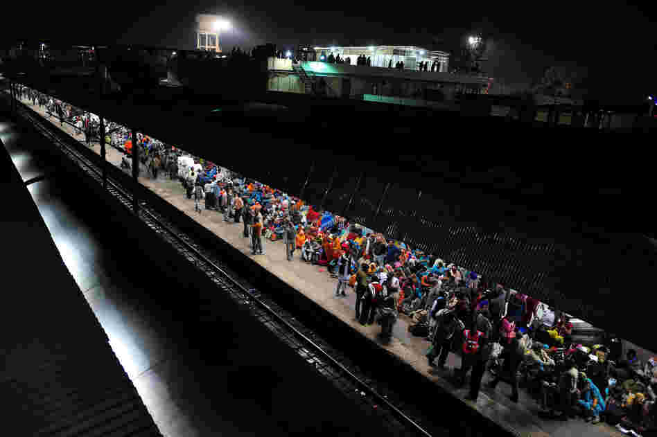 Hindu devotees wait Monday to board a train at the site of Sunday's stampede. Survivors blamed the tragedy on baton-charging police and the slow response of medics.