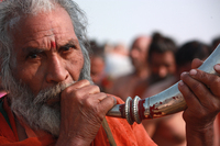 A man blows a horn in celebration during the daylong procession that drew 30 million devotees Sunday, the most auspicious day of the 55-day-long Hindu festival.