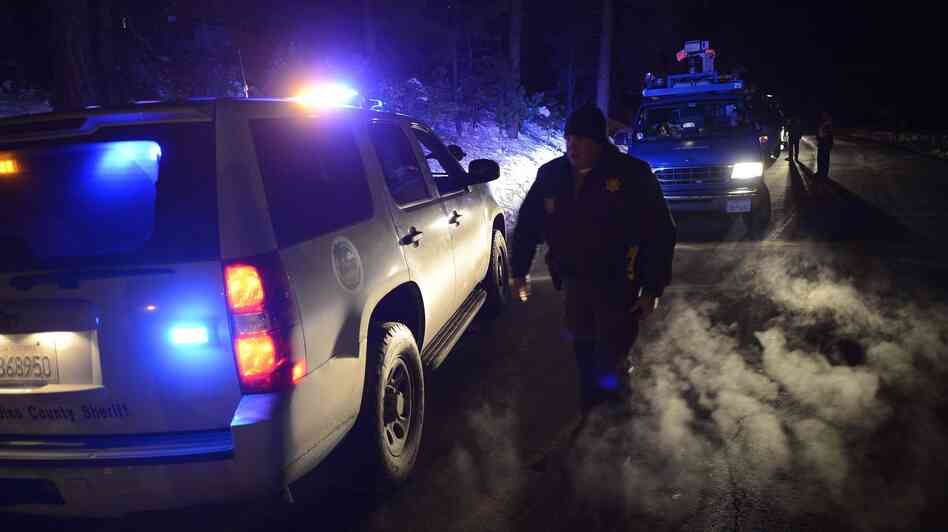 Police patrol a road block on Highway 38 into the Big Bear area where a shoot-out with suspected fugitive Christopher Dorner resulted in the death of one deputy in Angelus Oaks, Calif., on Tuesday.