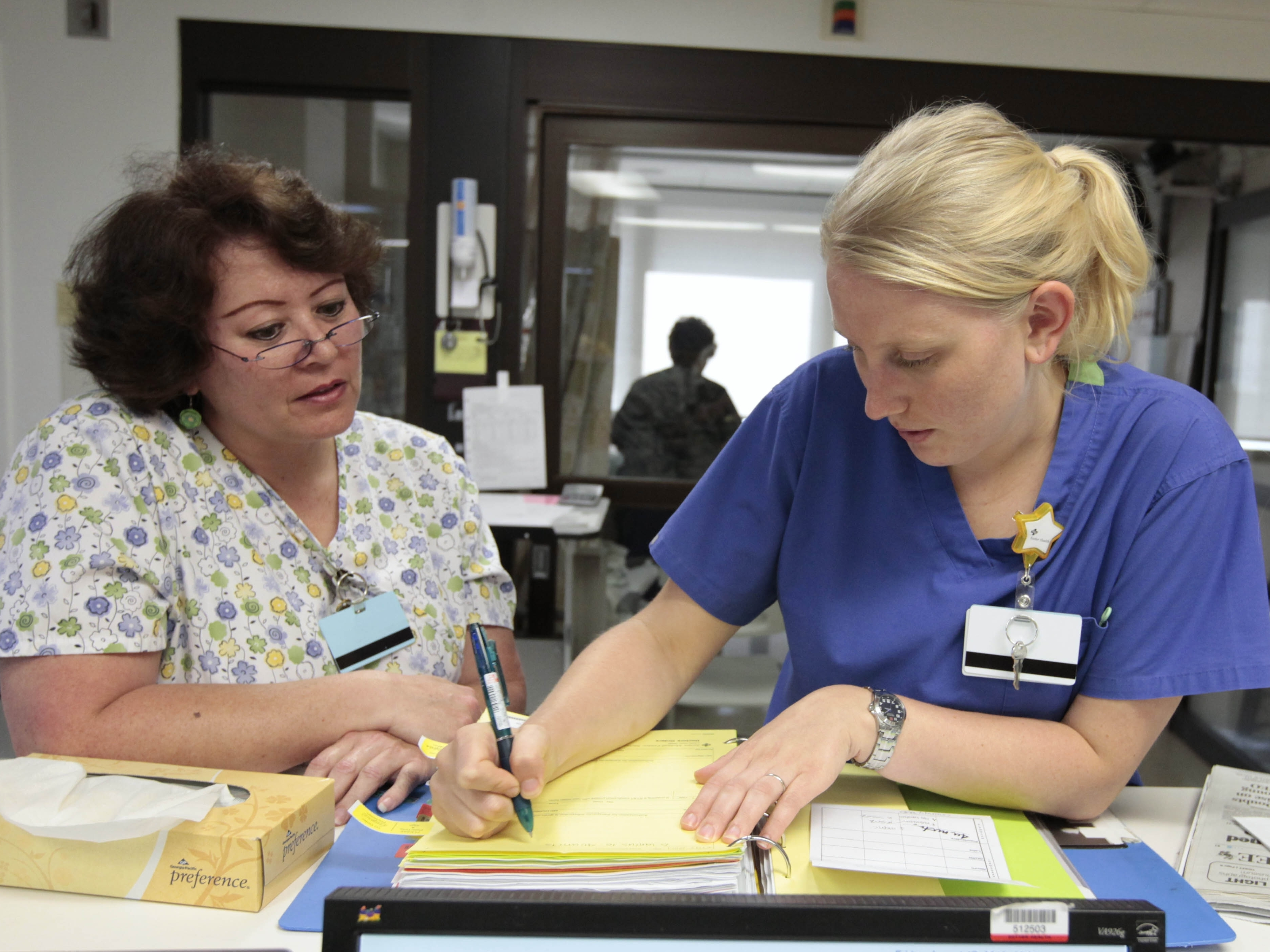 Kathryn Gilles, a new registered nurse at Sutter Memorial Hospital, in Sacramento, Calif., puts information into a patient's chart under the supervision of her mentor, Eileen Anderson, R.N., BSN.