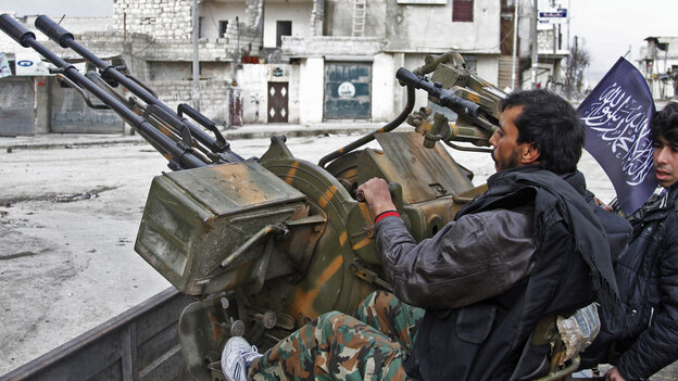 Syrian rebels say they captured an important military air base in northern Syria on Tuesday. Here, rebels sit behind an anti-aircraft weapon in the northern city of Aleppo on Friday.