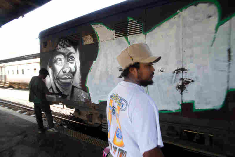 """27-year-old Uhuru B has been a graffiti artist for 12 years. """"What we're doing here now is part of a civic education, and also a way to advertise peace,"""" he says."""