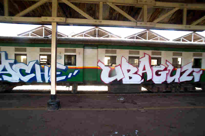 """""""Tuwache Ubaguzi"""" is part of a longer phrase written across the 10-car train, quoting the first line of a poem composed by a 13-year-old girl from Kibera. The full text translates to """"Down with tribalism, down with discrimination, let's live in peace."""""""