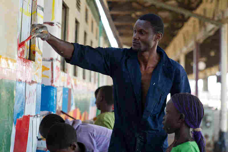 "Stephen Onyango Owino paints the train with the help of kids from ""Kibera Hamlets,"" a group that works with orphans and underprivileged kids in the Kibera slum."