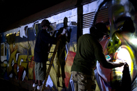 The artists work into the night to finish painting the peace train before it leaves for Kibera the next morning at 6 a.m.