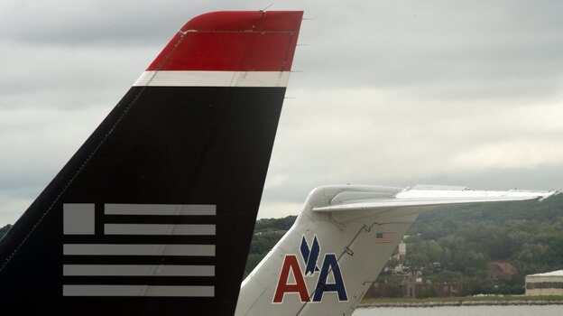 A US Airways jet rests on the tarmac near an American Airlines plane at Ronald Reagan Washington National Airport in Arlington, Virginia. (AFP/Getty Images)