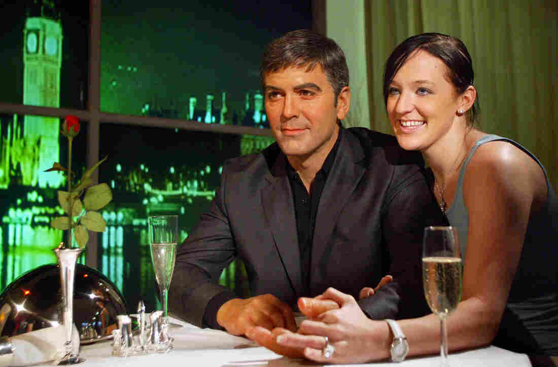 Staff member Kim Lee of Madame Tussauds wax museum poses with Wax George Clooney in 2004.