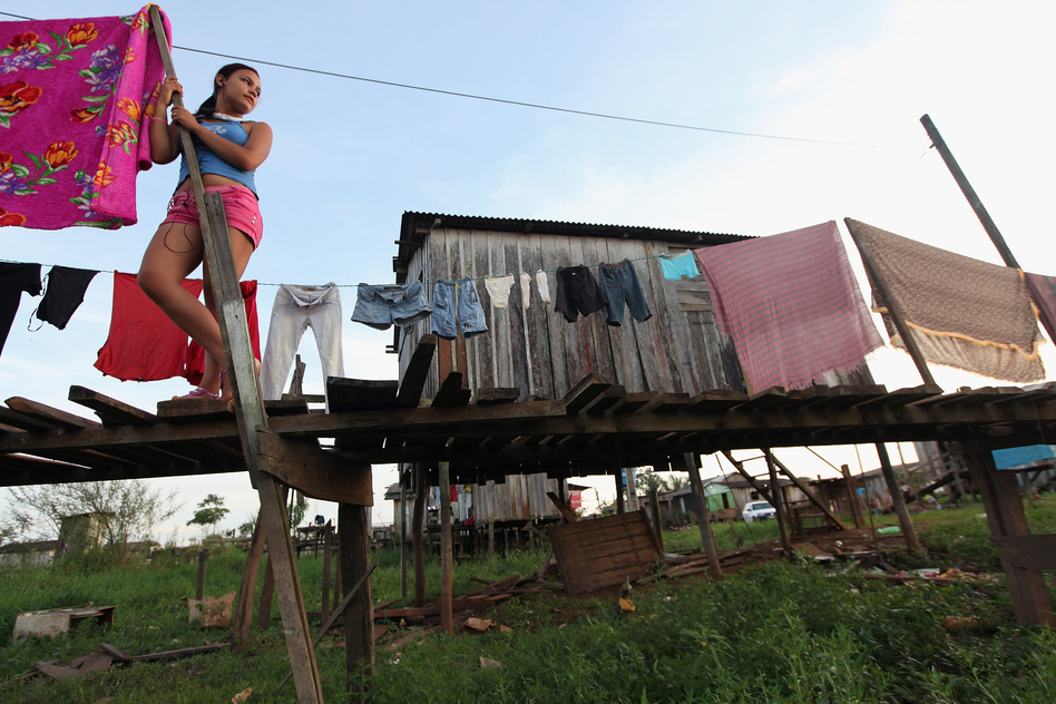 A resident stands in the low-lying Invasao dos Padres neighborhood, which stands to be flooded by the Belo Monte dam. Houses are constructed on stilts to protect against seasonal flooding. The government says residents forced to relocate because of the dam will be compensated, and that most will benefit from relocation. (Getty Images)