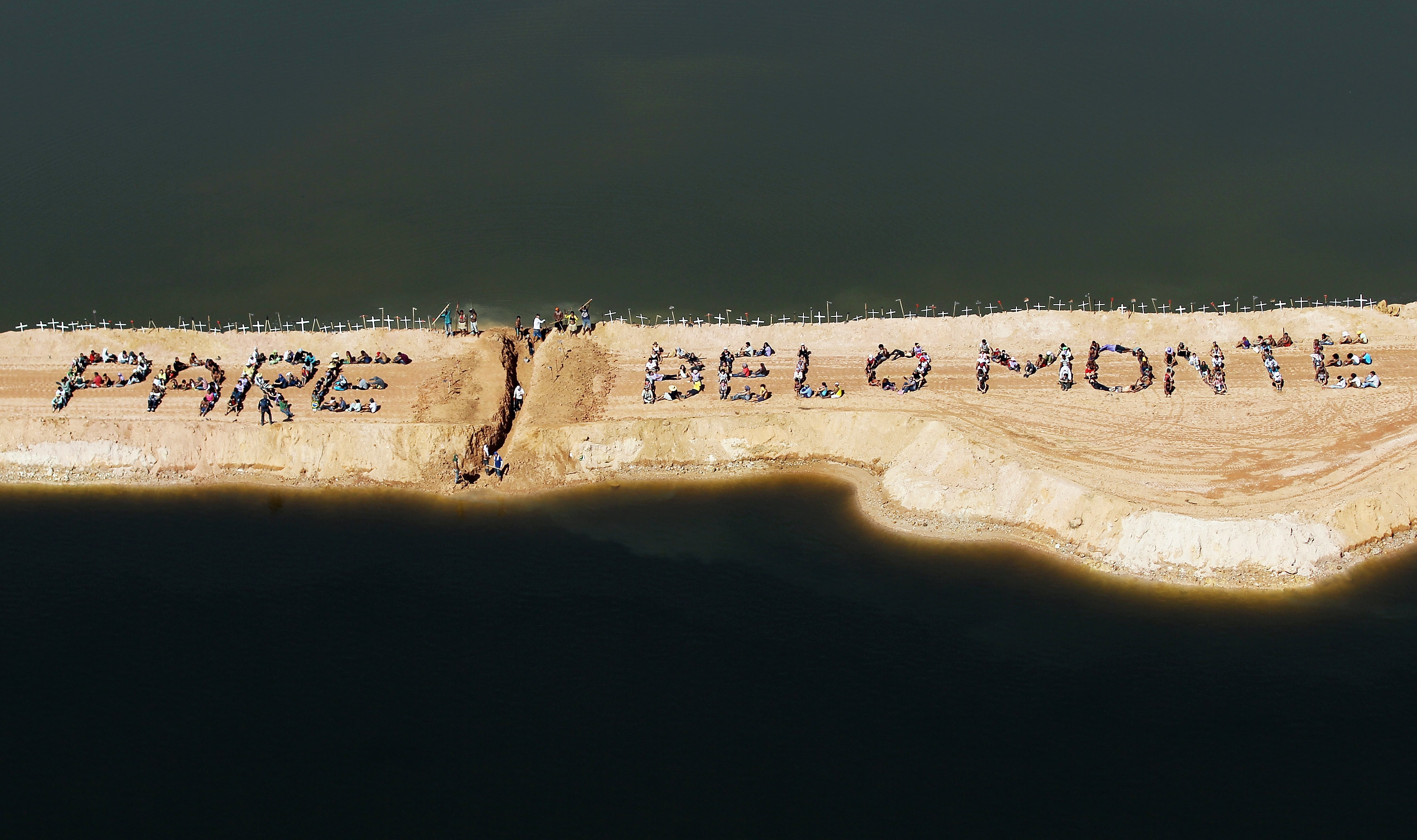 "Residents affected by the Belo Monte dam and their supporters stand atop a temporary earthen dam spelling out the words ""Pare Belo Monte,"" meaning ""Stop Belo Monte,"" at the dam construction site last June. Demonstrators also removed a strip of earth to restore the flow of the Xingu River as a protest against the construction."