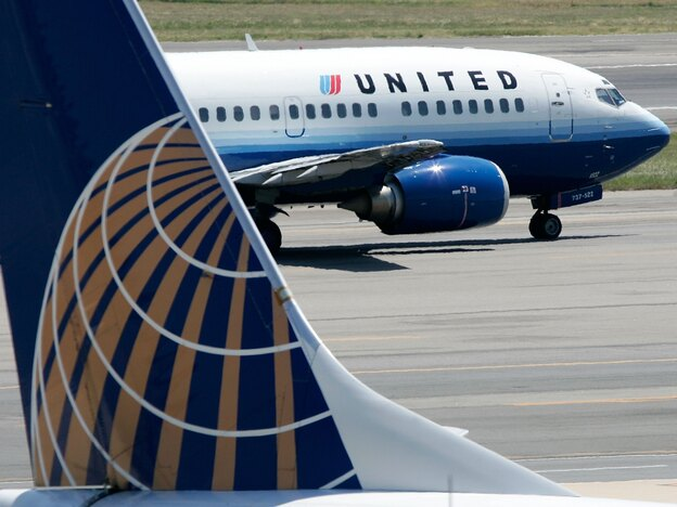 A United Airlines aircraft passes by a Continental Airlines plane at Ronald Reagan Washington National Airport in 2006. Their merger, begun in 2010, has been difficult, analysts say.