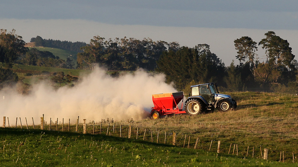 A tractor spreads fertilizer at a dairy farm in Morrinsville, New Zealand.