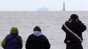 Spectators watch the Carnival cruise ship Triumph near Dauphin Island, Ala., Thursday, as the ship is towed to a