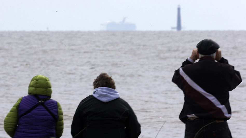 Spectators watch the Carnival cruise ship Triumph near Dauphin Island, Ala., Thursday, as the ship is towed to a terminal in Mobile. The Triumph is expected to arrive late Thursday night. (AP)